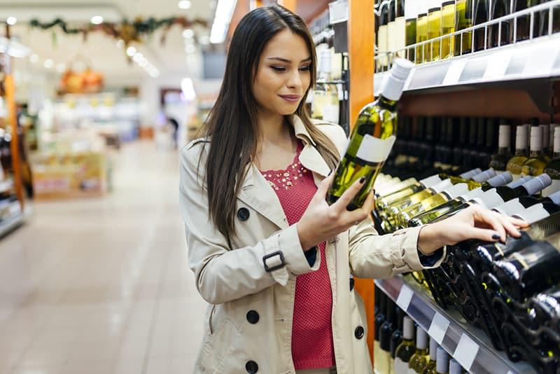 Eine Frau hält eine Flasche Wein im Supermarkt und entscheidet, welchen Wein sie kauft