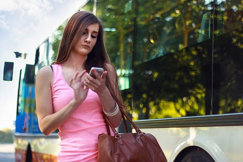 eine Frau mit ihrem Smartphone in der Nähe des Busses