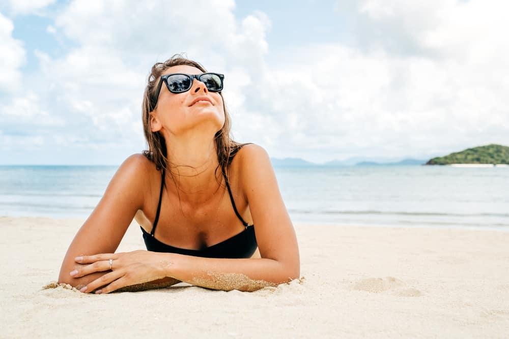 eine Frau sitzt am Strand