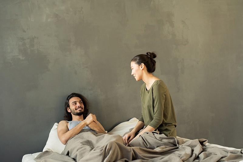 Eine Frau sitzt auf dem Bett neben einem Mann, der im Bett liegt und zusammen lacht