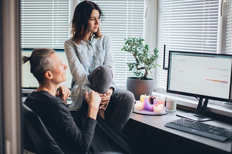 eine Frau sitzt auf dem Schreibtisch, während ihr Freund an einem Computer arbeitet