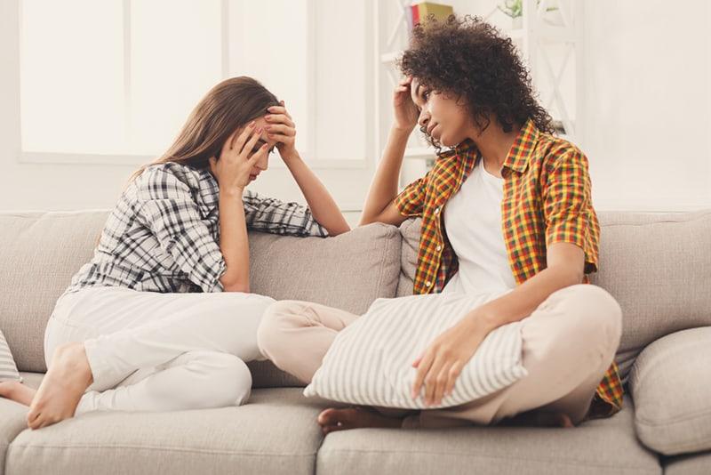 Eine Frau sitzt auf der Couch und hört einer traurigen Freundin zu, während sie über ihre Probleme spricht