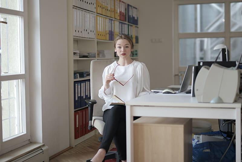 eine Geschäftsfrau, die am Schreibtisch sitzt und eine Brille hält