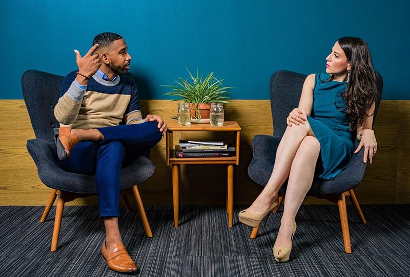 eine Geschäftsfrau, die ihrem männlichen Kollegen zuhört, während sie zusammen am Tisch sitzt