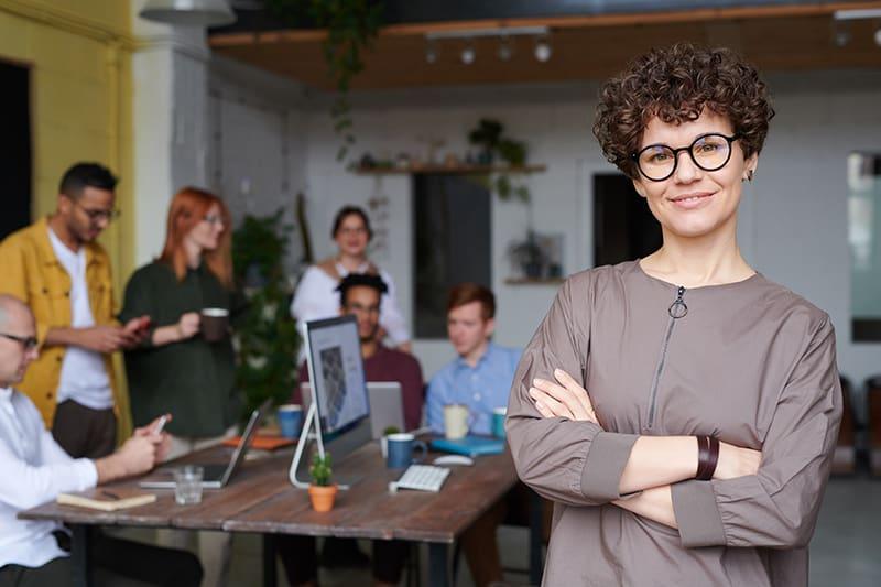 eine Geschäftsfrau, die mit verschränkten Armen im Büro steht, während ihre Kollegen hinter ihr arbeiten