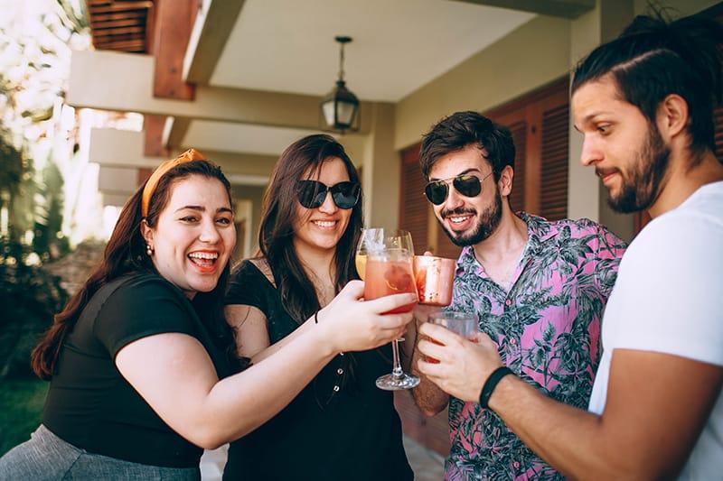 eine Gruppe von Freunden, die einen Toast mit einem Glas Getränk machen