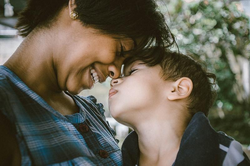 Eine Mutter und ihr Sohn berühren sich mit der Stirn