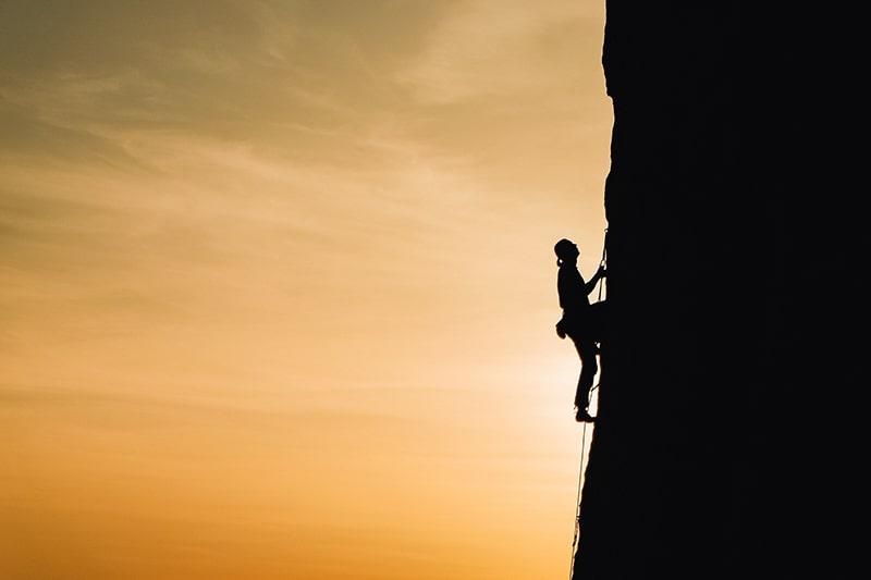 eine Person, die während des Sonnenuntergangs auf den Felsen klettert