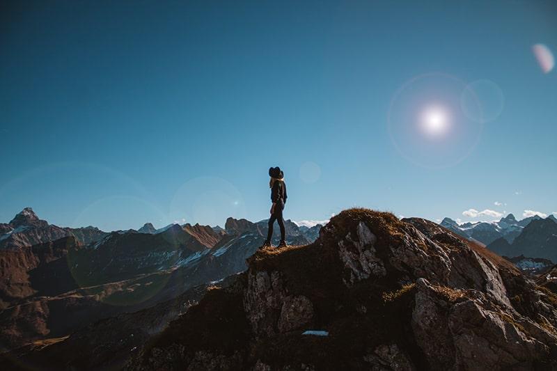 eine Person, die auf der Klippe mit Blick auf die Berge steht