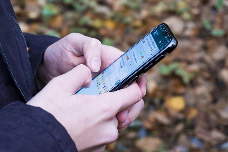 Eine Person, die während der Verwendung der Chat-Anwendung auf einem Smartphone tippt