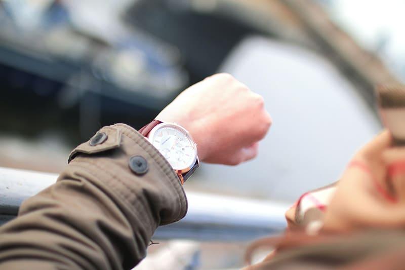 eine Person, die die Uhrzeit auf der Uhr überprüft, während sie auf jemanden wartet