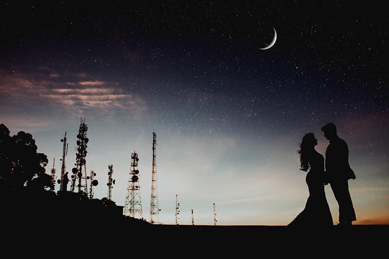 eine Silhouette des Paares, das in der Nacht unter dem Sternenhimmel steht