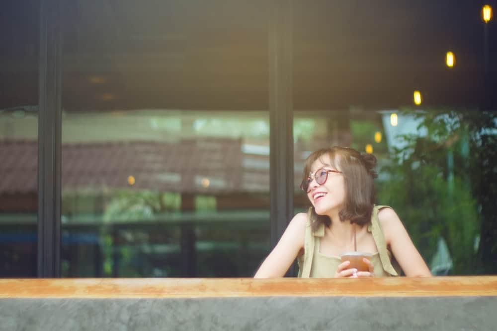 eine asiatische Frau mit Brille mit einem Lächeln denkt nach