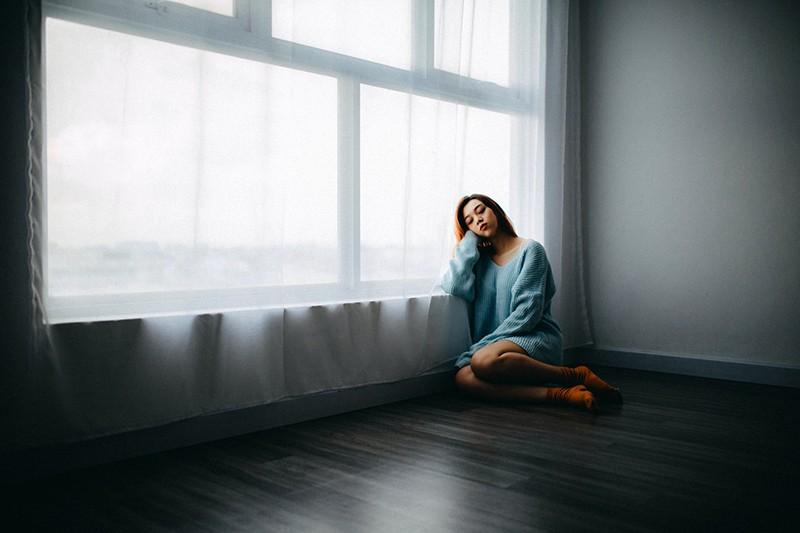 eine depressive Frau sitzt auf dem Boden neben dem Fenster