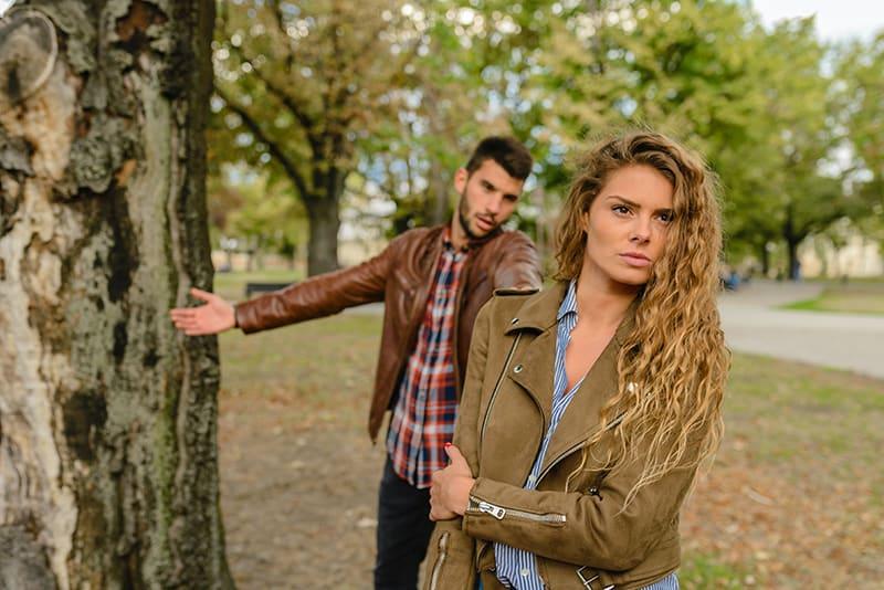 eine enttäuschte Frau, die vor einem Mann steht und um Vergebung bittet