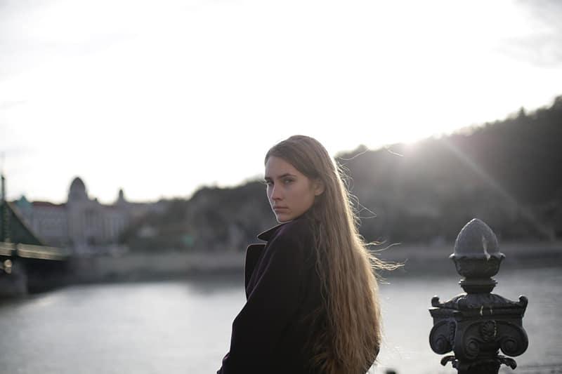 eine ernste Frau, die in der Nähe des Gewässers steht und über die Schulter schaut