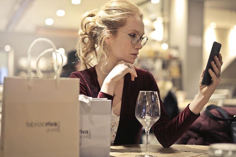 eine ernsthafte Frau, die auf ihr Smartphone schaut, während sie das Kinn berührt