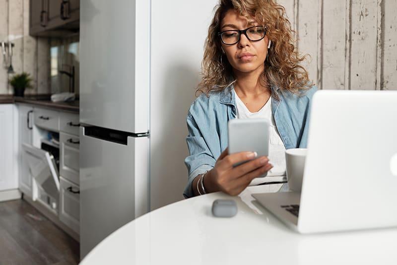 eine ernsthafte Frau, die ein Smartphone benutzt, während sie vor dem Laptop sitzt