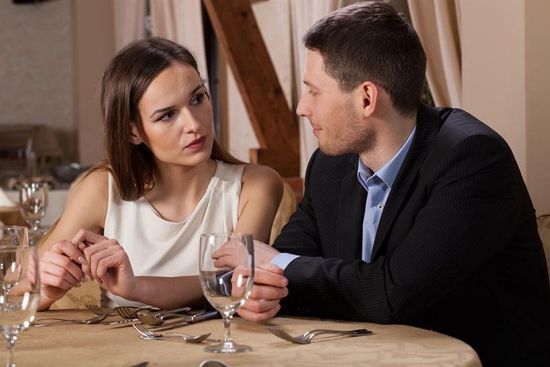 eine ernsthafte Frau, die einem Mann zuhört, während sie zusammen in einem Restaurant sitzt