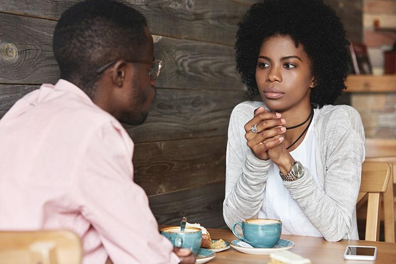 eine ernste Frau, die einen Mann während eines Gesprächs ansieht, während sie im Café sitzt
