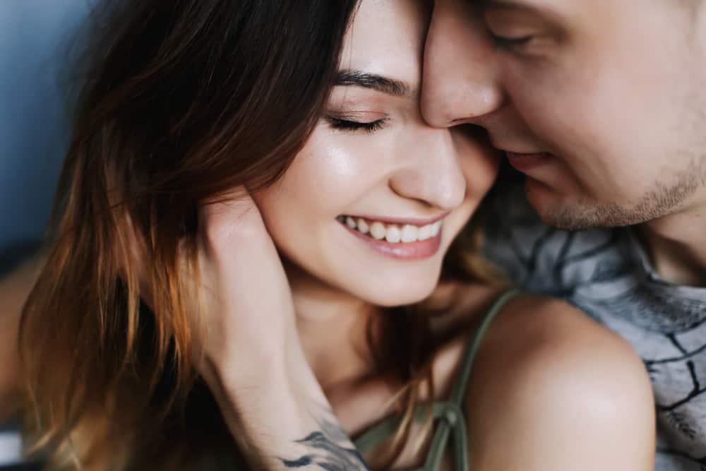 eine glückliche Frau in den Armen ihres Mannes, der ihren Hals streichelt