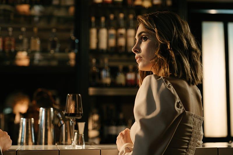 eine hübsche Frau, die beiseite schaut, während sie an der Bartheke steht