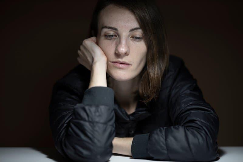 eine imaginäre Frau, die an einem Tisch sitzt