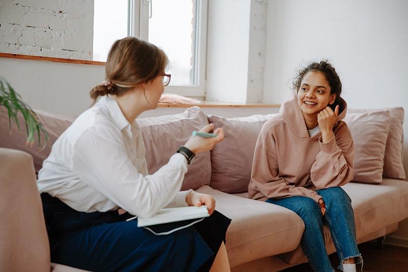 eine junge Frau, die mit einem Therapeuten spricht, während sie zusammen auf der Couch sitzt