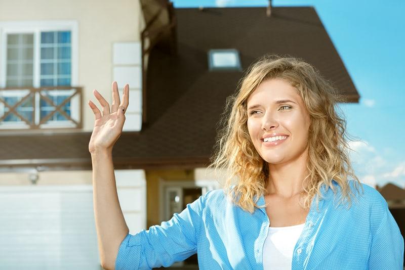 Eine junge Frau winkt den Nachbarn zu, während sie vor ihrem neuen Haus steht