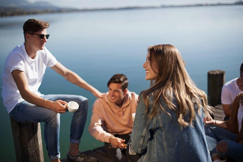 eine junge lächelnde Frau, die mit Freunden auf dem Bootssteg sitzt