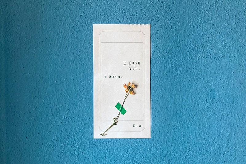 eine kurze Liebeserklärung auf weißem Papier mit einer Blume darauf