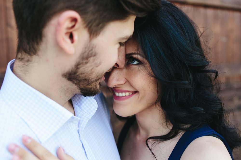 eine lächelnde Brünette in der Umarmung ihres Mannes