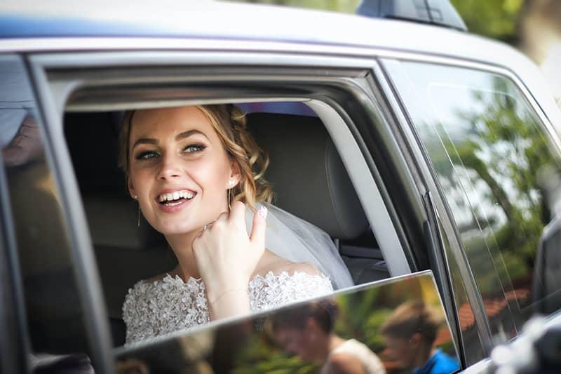 eine lächelnde Braut, die im Auto sitzt und durch das Fenster schaut
