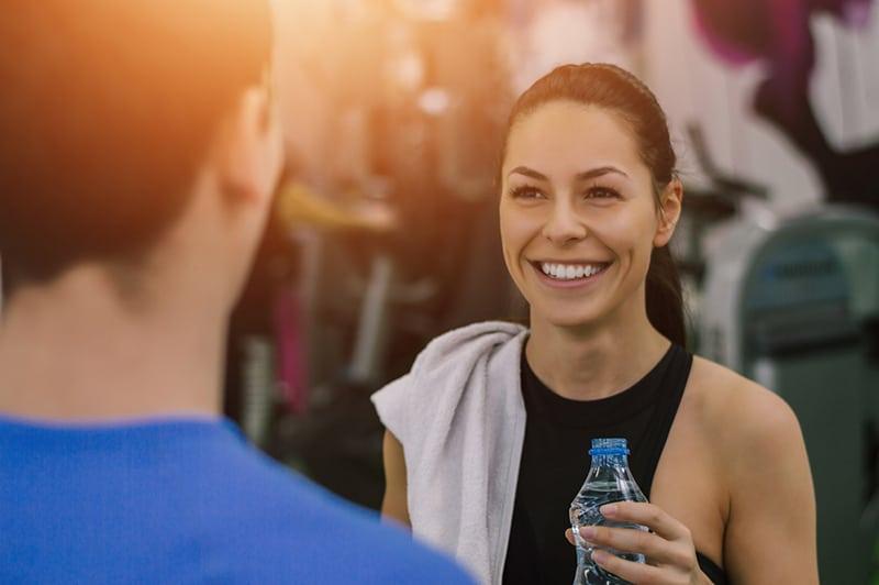 eine lächelnde Frau, die Wasserflasche im Fitnessstudio hält, während sie vor einem Mann steht