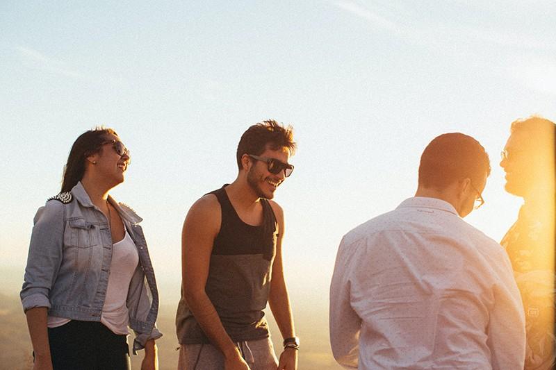 eine lächelnde Frau, die Zeit mit Freunden draußen während des Sonnenuntergangs verbringt