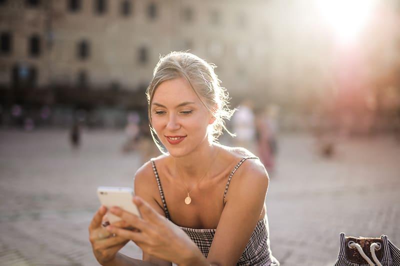 eine lächelnde Frau, die auf dem Smartphone eine SMS schreibt, während sie auf dem Platz sitzt