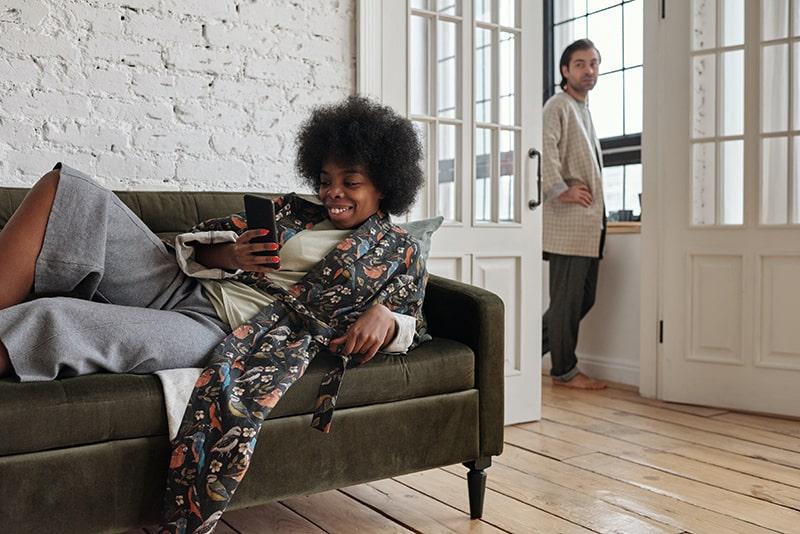 eine lächelnde Frau, die auf dem Sofa sitzt und ein Smartphone benutzt, während ihr Mann am Fenster steht und sie ansieht