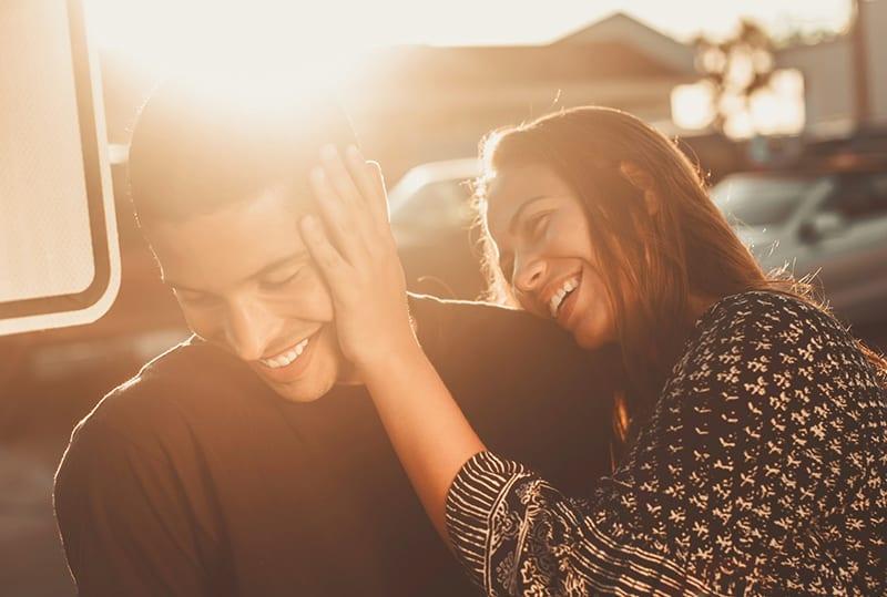eine lächelnde Frau, die das Gesicht des Mannes berührt, während er auch lächelt