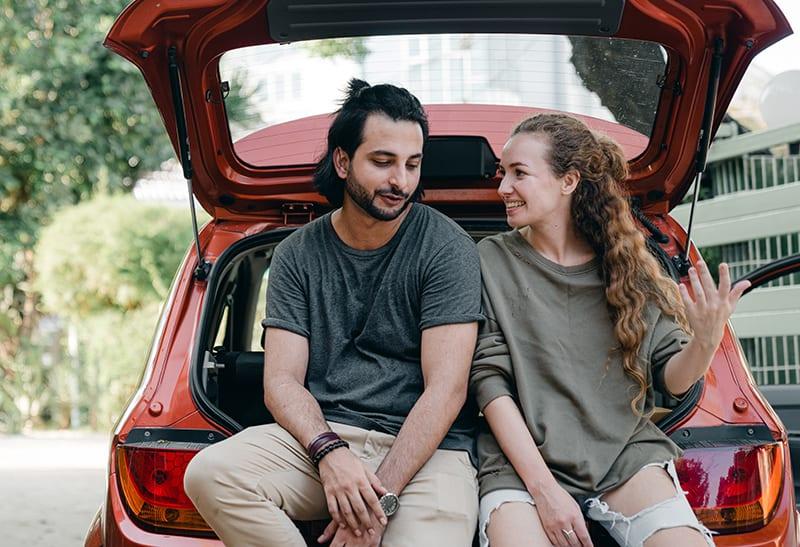 eine lächelnde Frau, die einem attraktiven Mann während eines Gesprächs beim Sitzen auf einem Autokofferraum zuhört