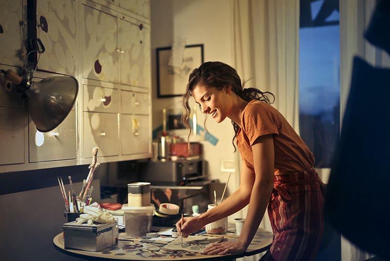 eine lächelnde Frau, die malt, während sie am Tisch im Atelier steht