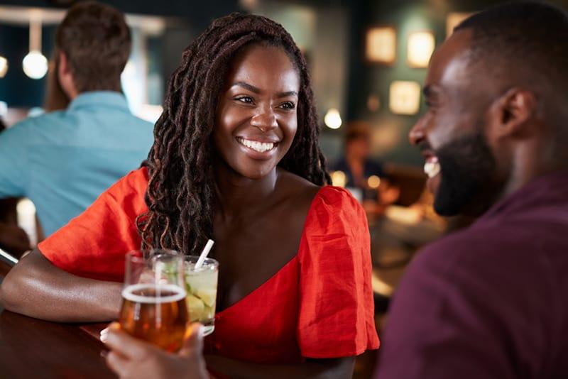 eine lächelnde Frau, die mit einem Mann an der Theke sitzt und zusammen etwas trinkt