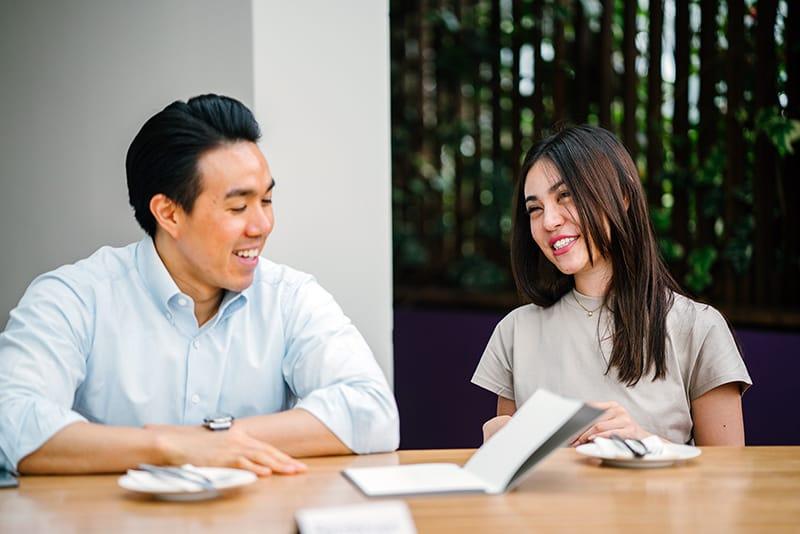 eine lächelnde Frau, die mit einem Mann spricht, während sie am Tisch sitzt