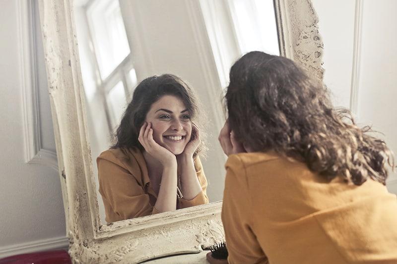 eine lächelnde Frau, die sich in den Spiegel schaut, während sie sich auf das Regal lehnt