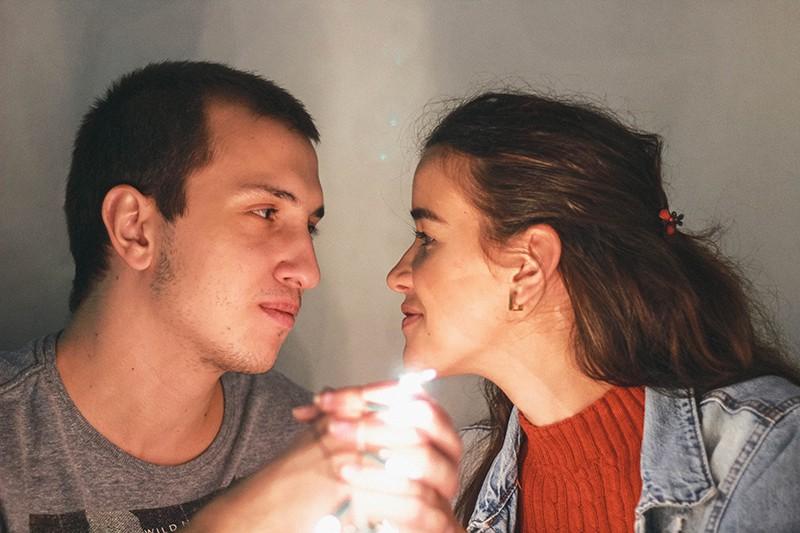eine lächelnde Frau gegenüber einem Mann, während beide Hände halten