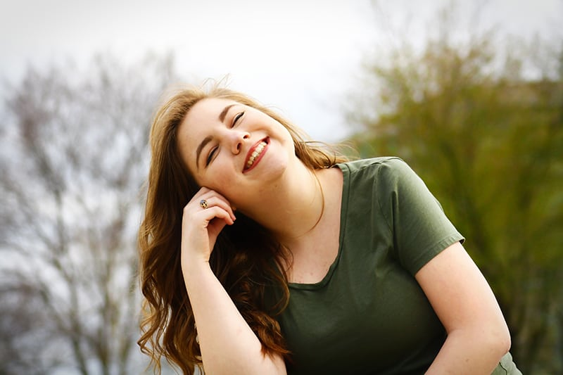 eine lächelnde Frau in einem grünen Hemd, während sie ihre Wange berührt