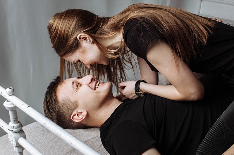 eine lächelnde Frau, die auf ihrem Freund sitzt, während er auf einem Bett liegt