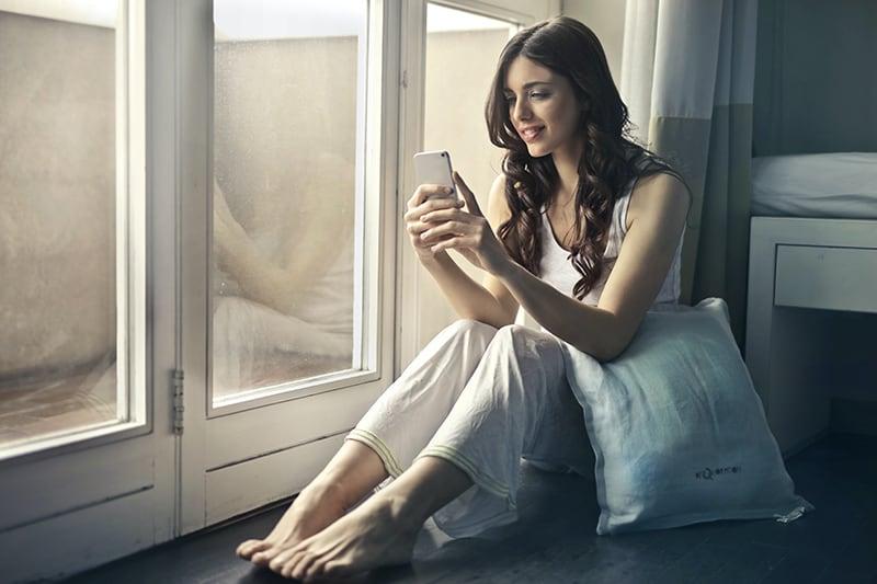 eine lächelnde Frau, die neben dem Fenster sitzt, während sie ein Smartphone benutzt