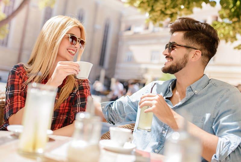 eine lächelnde Frau und ein lächelnder Mann, die an einem Date im Café sitzen