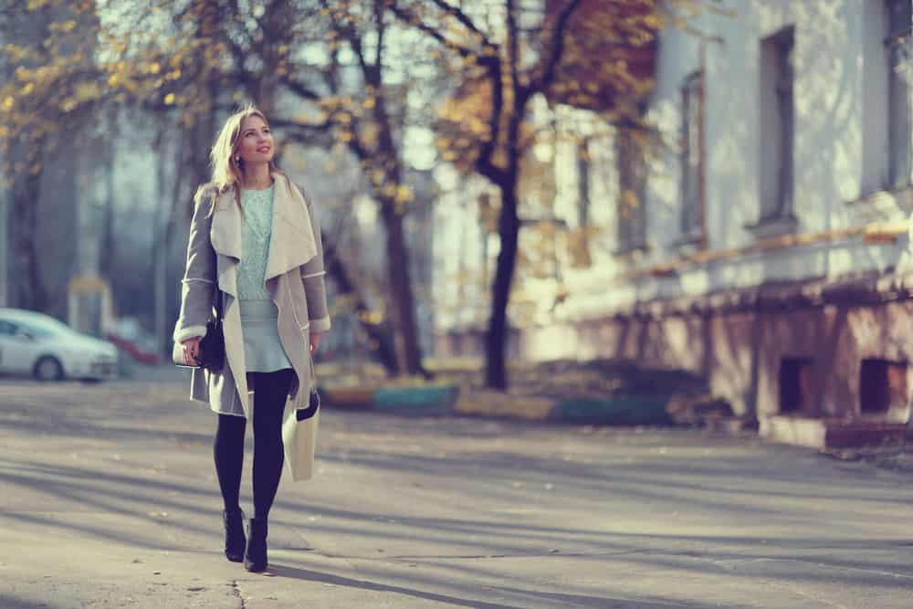 eine lächelnde Geschäftsfrau, die im Herbst die Straße entlang erntet