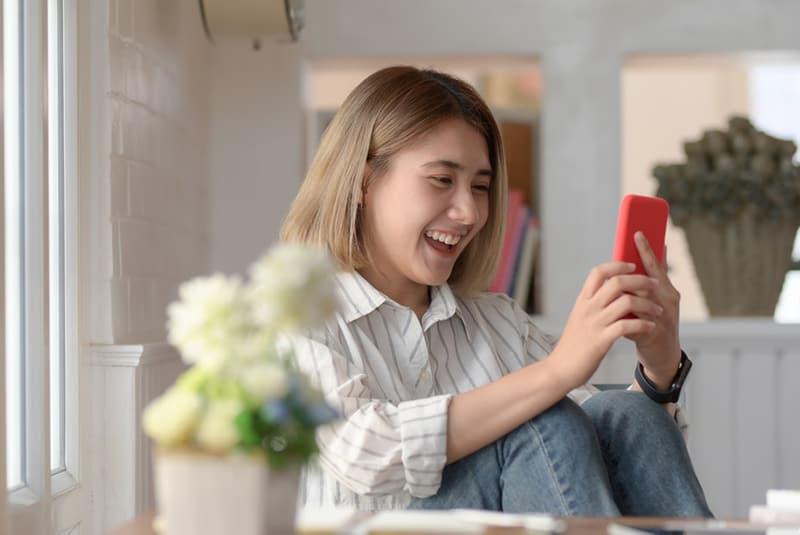 eine lachende Frau, die eine Nachricht von einem Smartphone liest, während sie auf dem Stuhl sitzt